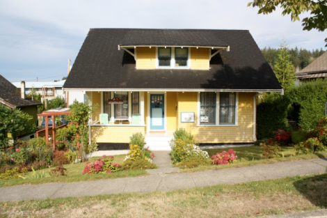 The yellow Postmasters house – a classic bungalow with a front porch and shed dormer