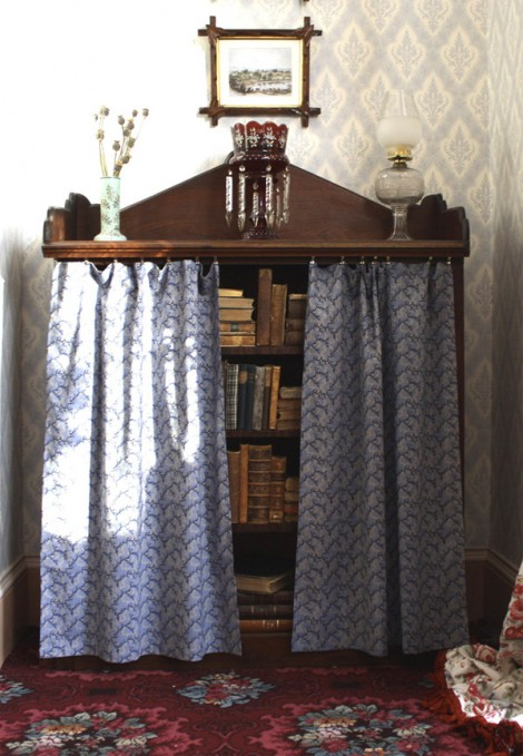 Bookcase c. 1865 in Gothic Revival style. The picture frames are hanging from wires connected to a 'picture spike' at the cornice level. The frames with the crossed corners are 'Oxford frames', a style particularly popular in the 1860's.  The curtains were originally hung to protect the leather bindings from sunlight. The wallpaper is an exact reproduction of the original first installed in 1865.