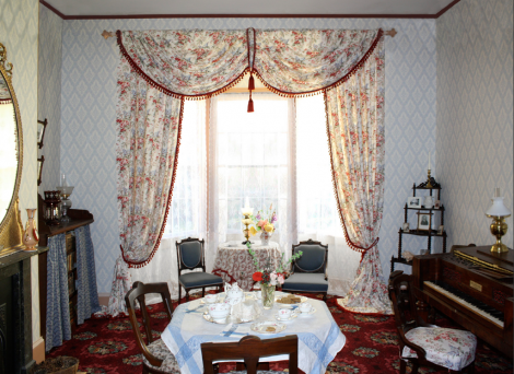 The restored Drawing Room of an 1865 modest Gothic Revival house in Victoria Canada. The wallpaper and border are exact reproductions of the originals. The curtains are hung in the original location in front of the bay window. The corner whatnot and piano are on the original inventory.
