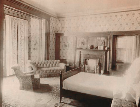 "A light and airy guest bedroom in the Cupples home - seen shortly after construction - belies the rough masonry that envelops it on the outside. The wallpaper and fabric used on the window pelmet is William Morris' ""Garden Tulip"", which gave a light floral motif to the interior decoration."
