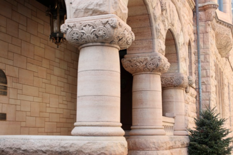 The entrance porch, seen here in a 2010 photograph, features three typical Richardson Romanesque squat columns with splendidly carved capitals.