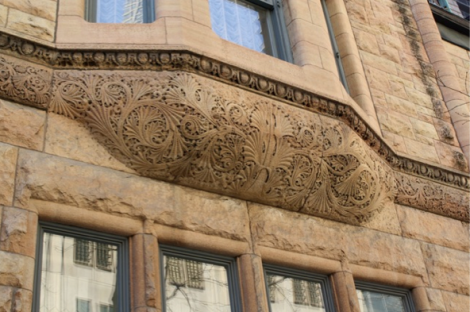 The carving under a second floor bay window is naturalistic in design, yet formal in layout, adding a lightness and delicacy to what could be a heavy feature of the building.