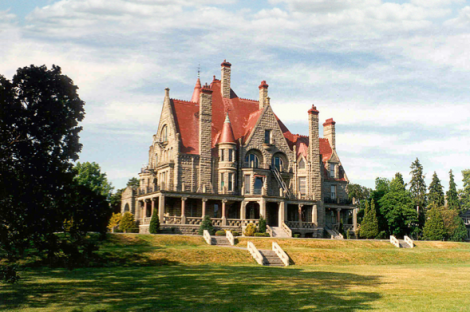 The garden front of Craigdarroch Castle, which was built in 1890 in Victoria, Canada for coal baron Robert Dunsmuir, who unfortunately died before the house was finished.  Richardson Romanesque details can be seen in the rough stonework, round-head arches, and the semi-tower on the south façade. Another taller tower rises above the porte cochere on the north side. The steep roofline, clad in red slate, contrasts well with the warm stone of the walls.   From the house, and especially from the upper rooms, turrets and balconies, are distant views over the City and the Straits of Juan de Fuca towards the Olympic Mountain range in Washington State over twenty miles away. The house is now a historic house museum and open to the public.  See their website: http://www.thecastle.ca/