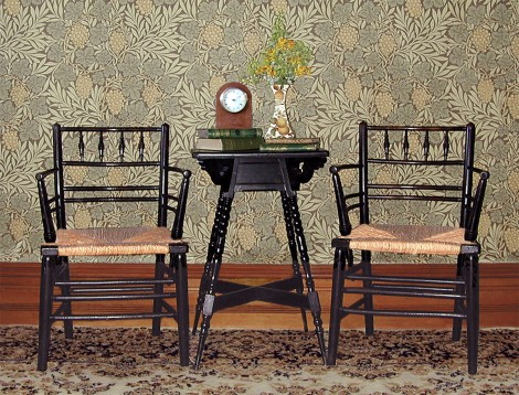 "A pair of William Morris' ""Sussex"" chairs, with rush seats, which were also available in armless versions. The wallpaper is Morris' ""Vine"" wallpaper, available in four colourways from www.CharlesRupertDesigns.com"